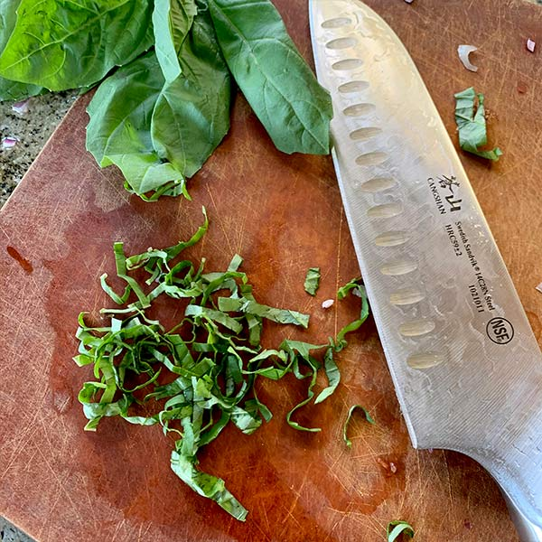 basil being cut by the Cangshan TC Series Sandvik Swedish Steel Forged 7-Inch Santoku Knife
