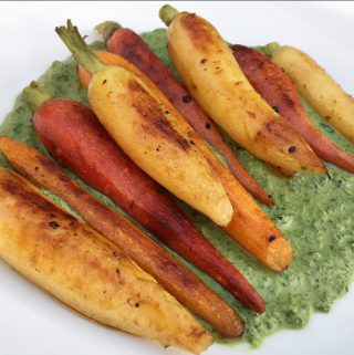 Grilled carrots on a bed of Creamy carrot top pesto